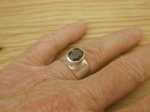 Thorite (Uranium Thorium Silicate) crystal in silver ring for accupuncture stimulation.